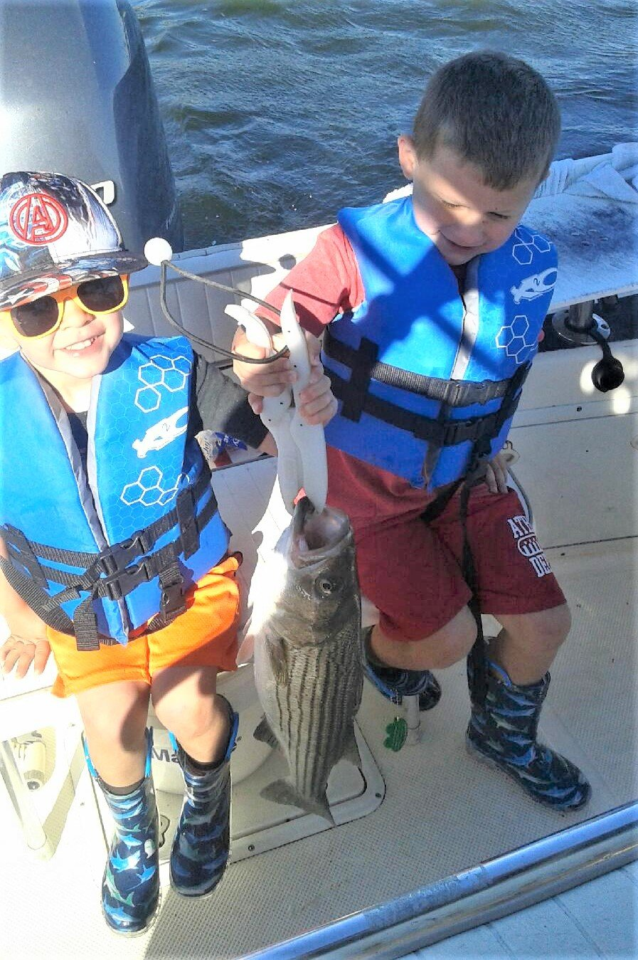 "First striped bass: Eli (3) and Andre (5) Swain of Richmond with their first striped bass when fishing with grandfather Mike Swain. They reeled in 22"" to 26"" fish trolling lures."