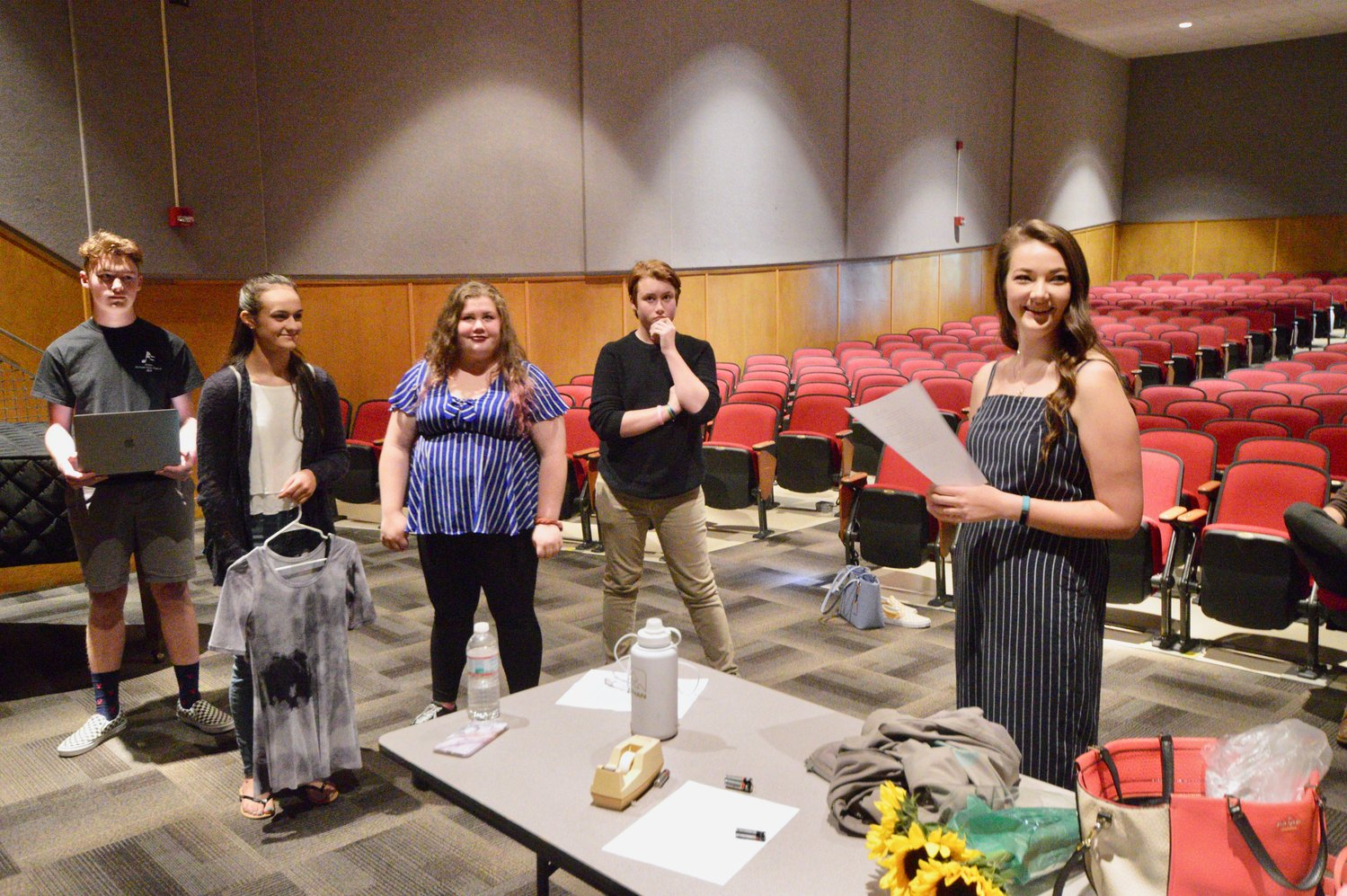 Portsmouth High School student Teagan deGroen (holding paper) runs through a checklist with performers during a rehearsal just hours before the real thing Saturday.