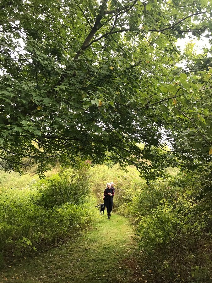 Susan Ruf of the Aquidneck Land Trust walks a path of Little Creek Preserve with Dennis Silvia, the previous landowner.