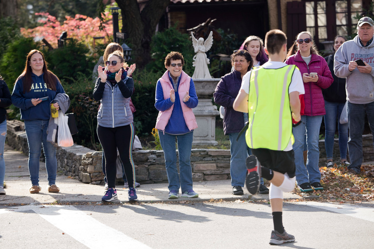 Spectators line Wilson Avenue to cheer for runners as they pass by while participating in the East Providence Firefighters Freaky 5k, Sunday.