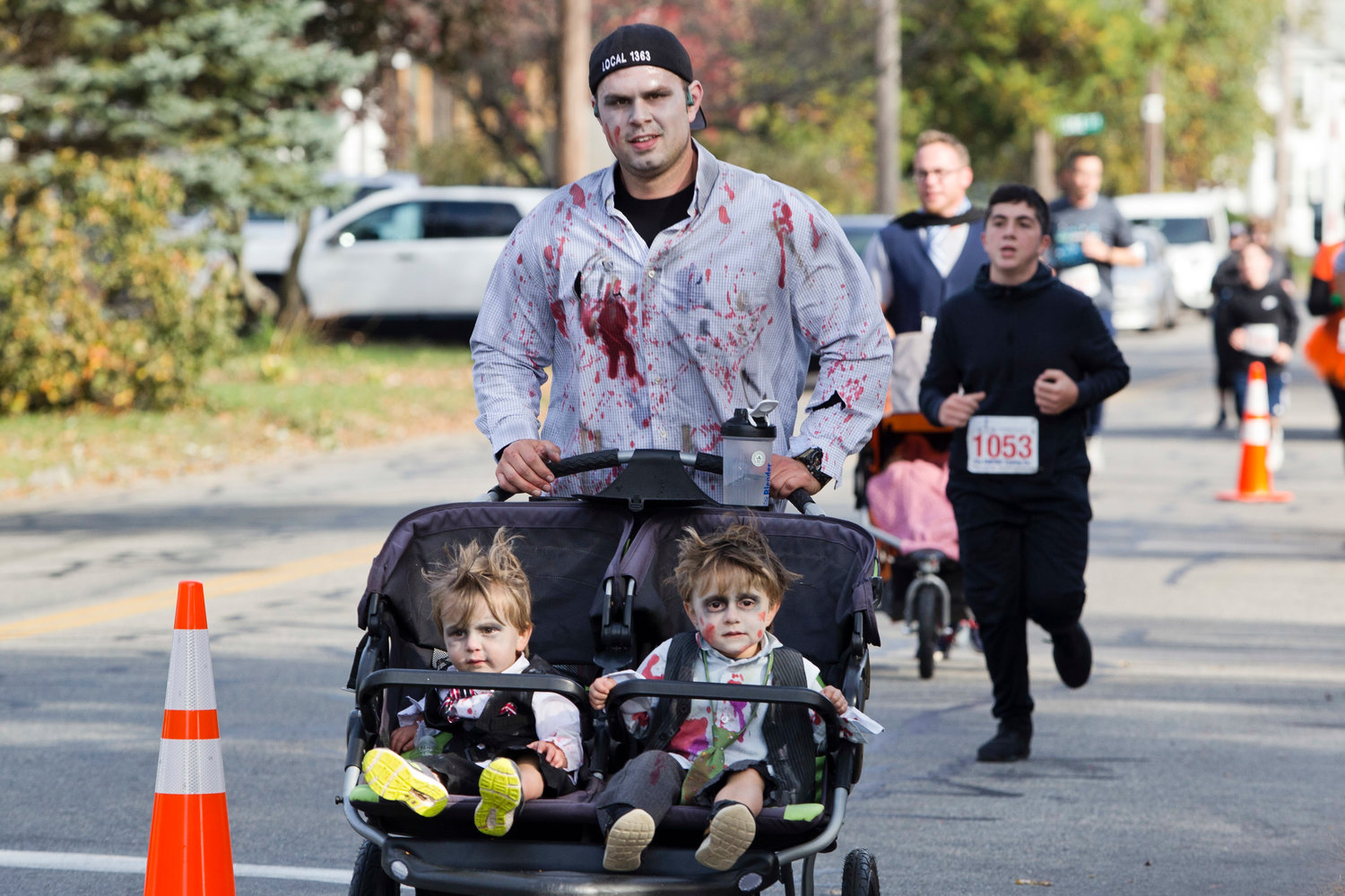 Corey Rebello pushes his zombie children, Granger (left) and Corbin (right) down Wilson Avenue while participating in the East Providence Firefighters Freaky 5k, Sunday.