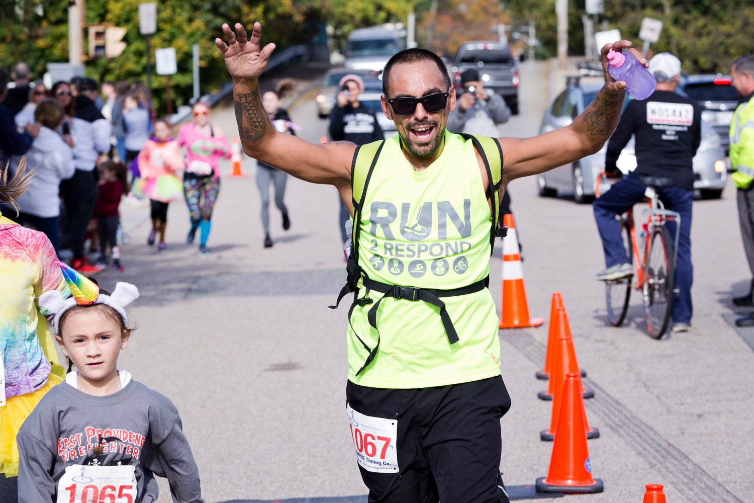 Jason Rudolf raises his arms in victory as he and his daughter, Bella run through the finish line of the East Providence Firefighters Freaky 5k, Sunday.