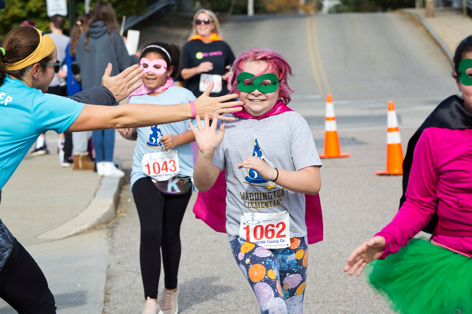 Kamryn Lindsey (left) and Alice Rouette (right) are offered high-fives as they cross the finish line of the East Providence Firefighters Freaky 5k, Sunday.