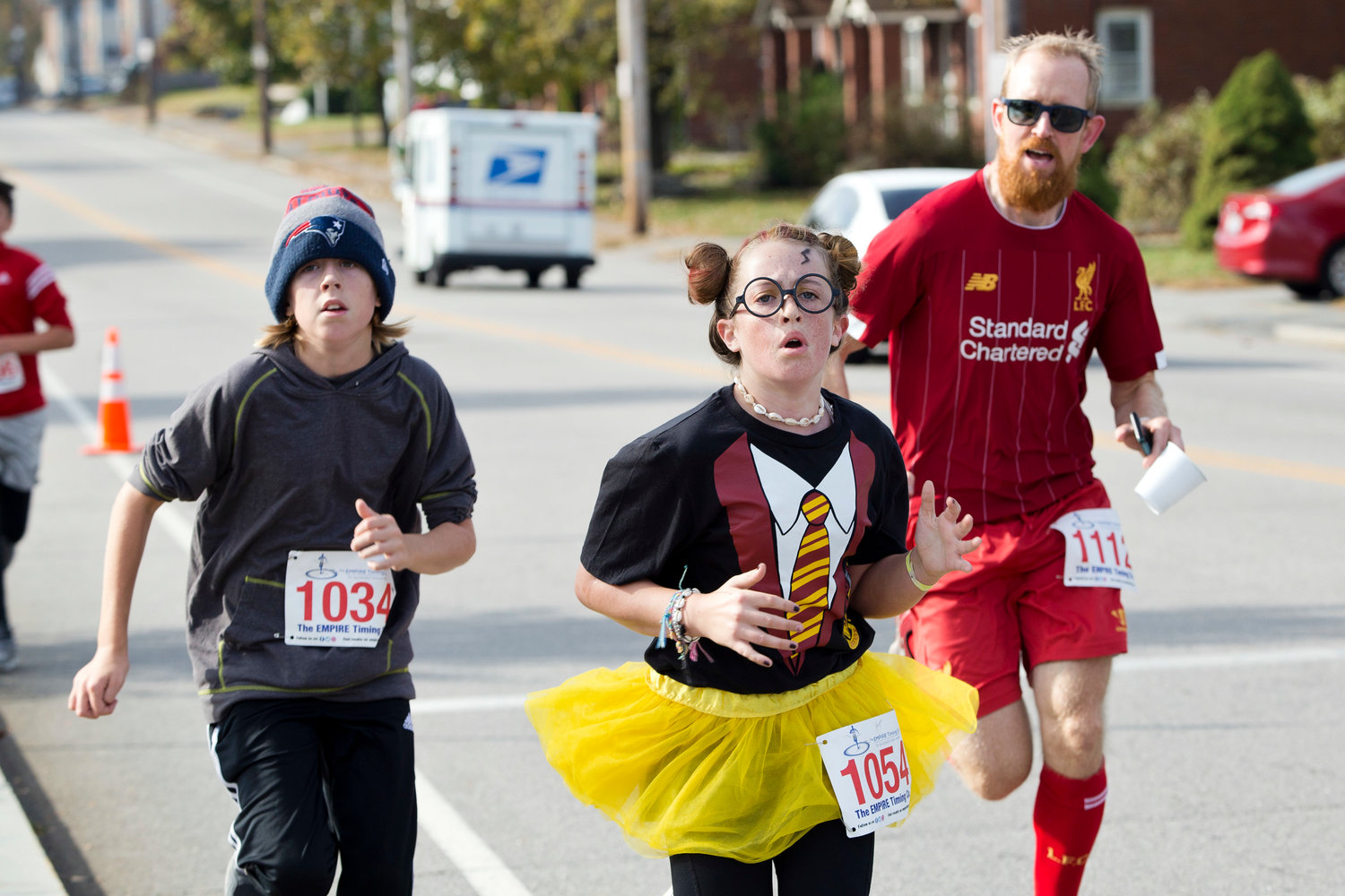 Luke Grimley, Hope Moran and Sturrt Moran make their way toward the finish line of the East Providence Firefighters Freaky 5k, Sunday.
