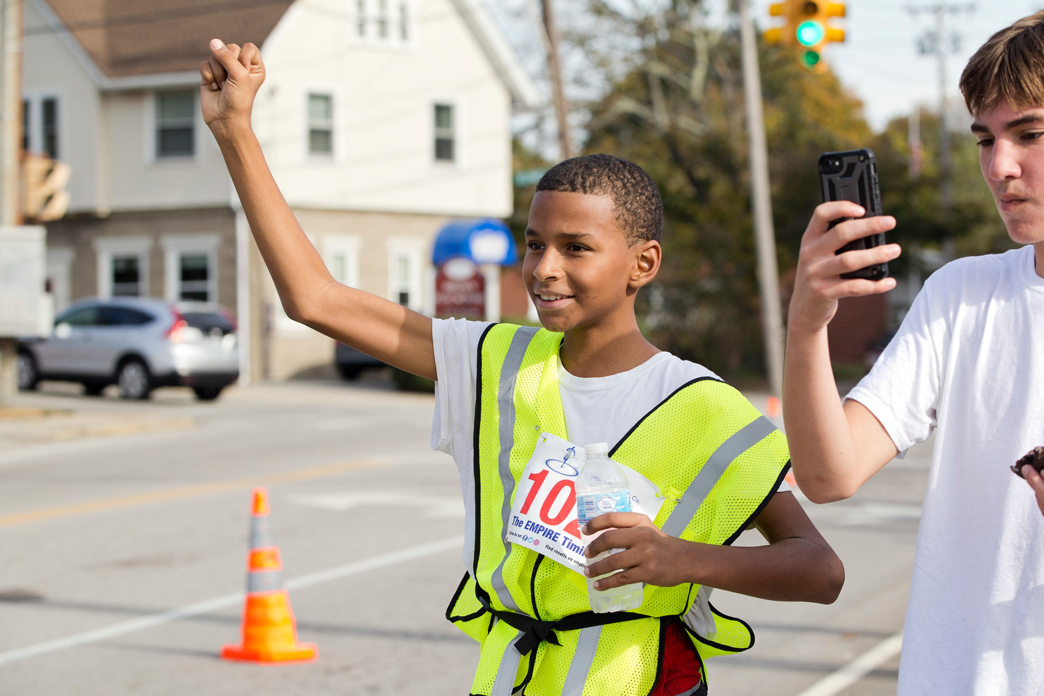 Jayden Delgado cheers for friends as they approach the finish line of the East Providence Firefighters Freaky 5k, Sunday.