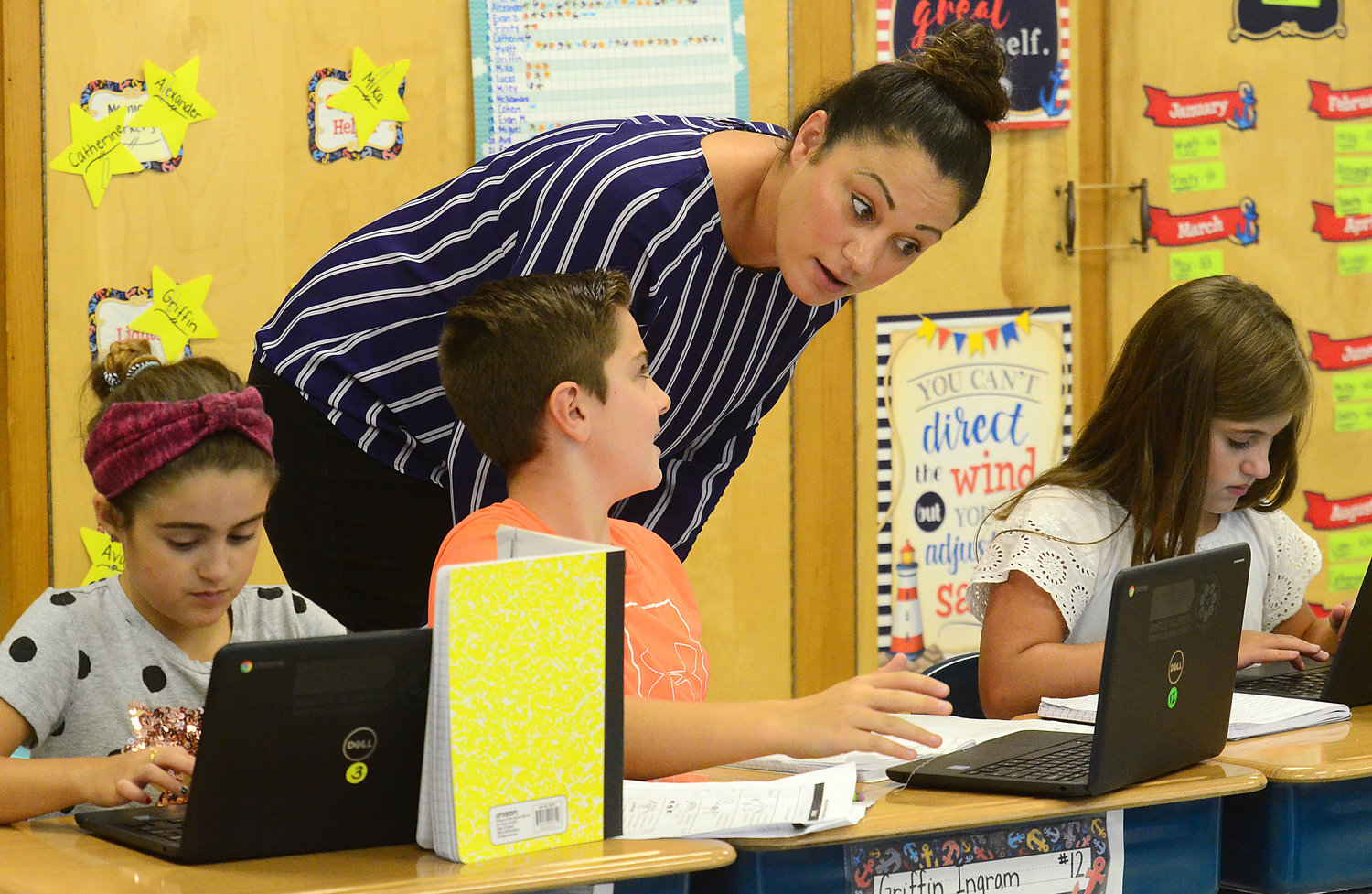 Fourth-grade teacher Amanda Lawlor talks ideas with Griffin Ingram (middle) with Oakley Centazzo (left) and Reese Rybak (right) during a Lucy Calkins writing workshop at Rockwell School on Wednesday.