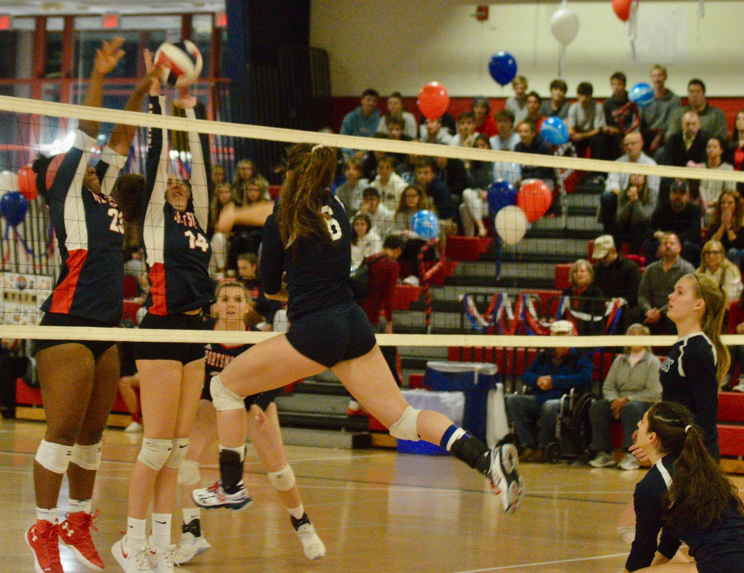 Gabby Bryan (left) and Jill Lunney go up for the block against Burrillville.