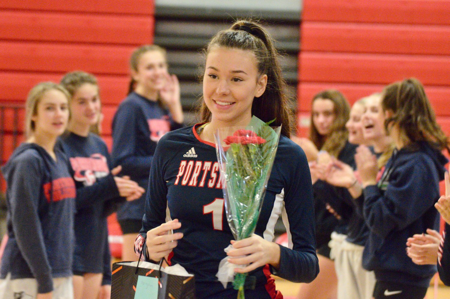 Morgan Shablom, a member of the PHS girls' volleyball team, smiles after receiving flowers after her introduction on Senior Night Monday.