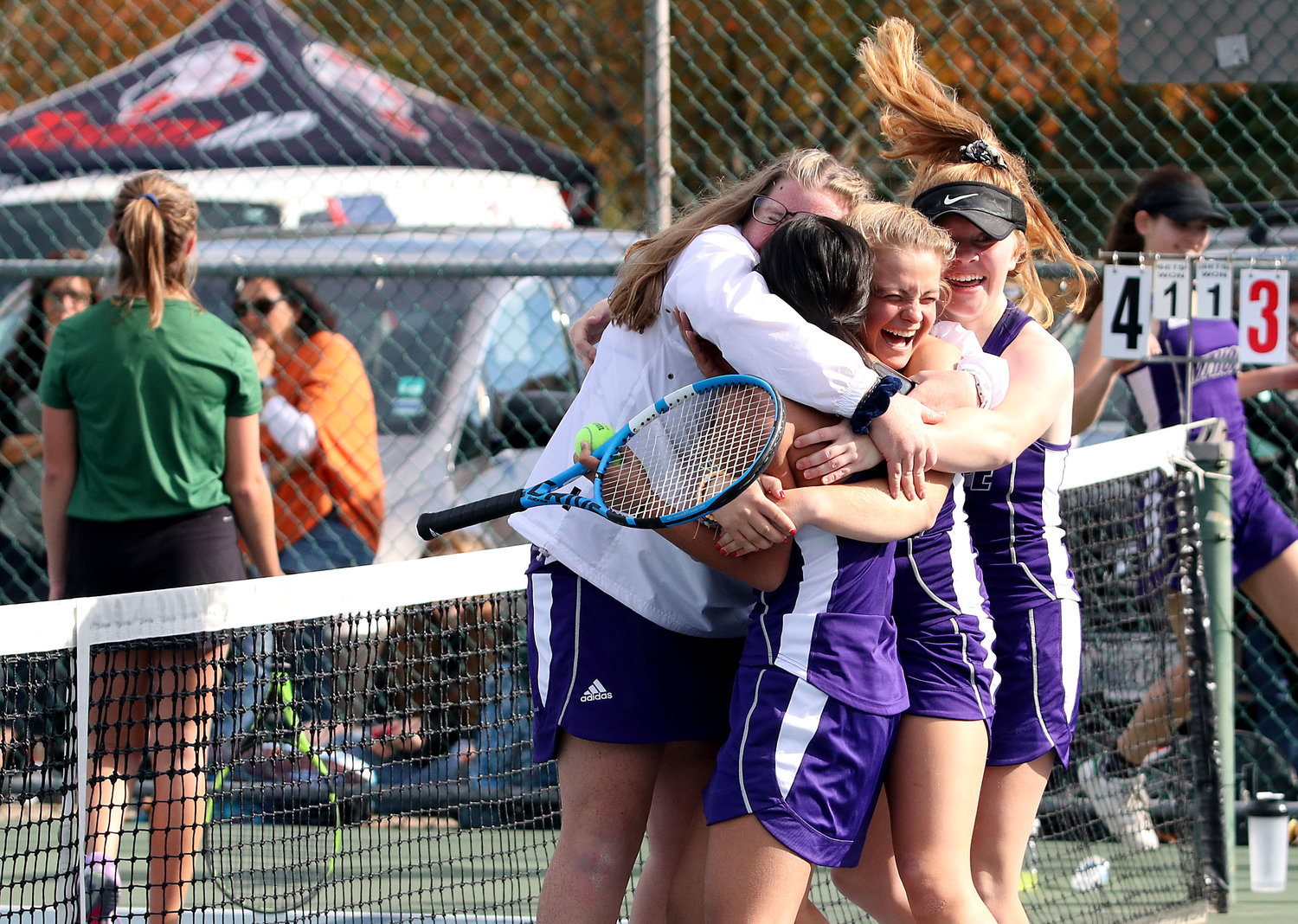 Jilly Parker (center), Meg Dolan (left) and other teammates swarm and hug No. 4 singles player Eva White after she clinched the State championship.
