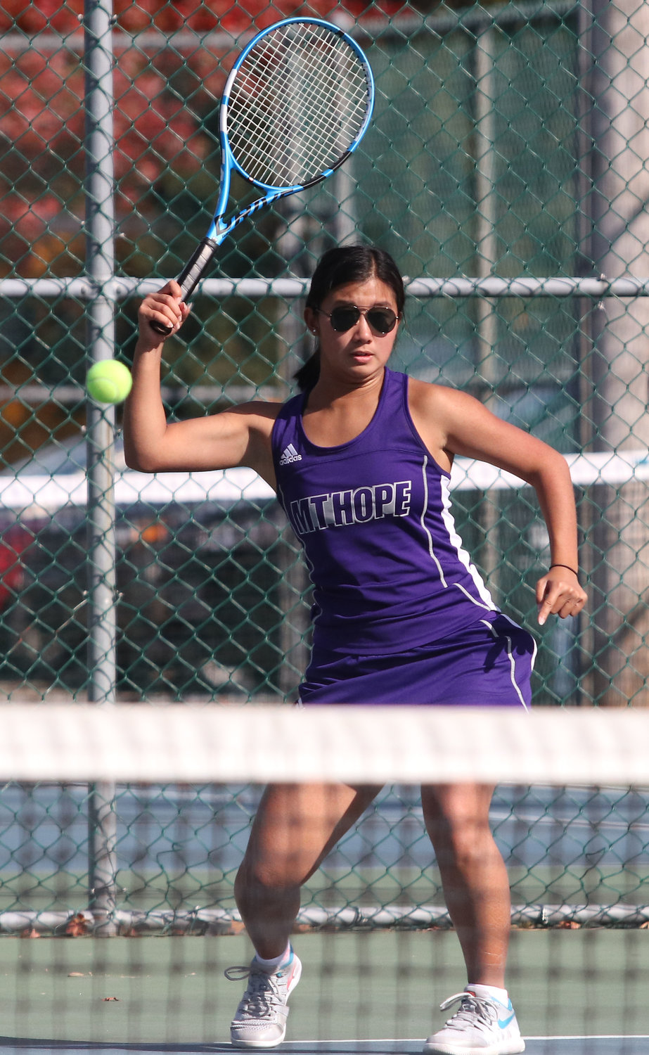 Eva White hits an overhand during her match. She won the fourth point and clinched the match for the Huskies.