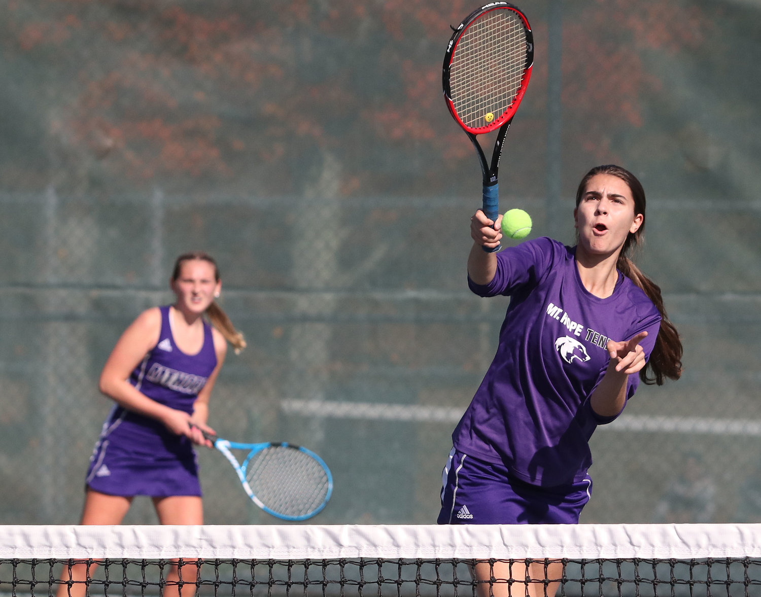 Marisa Astrologo (right) hits a winner from her position at the net with No. 2 doubles team partner Catherine