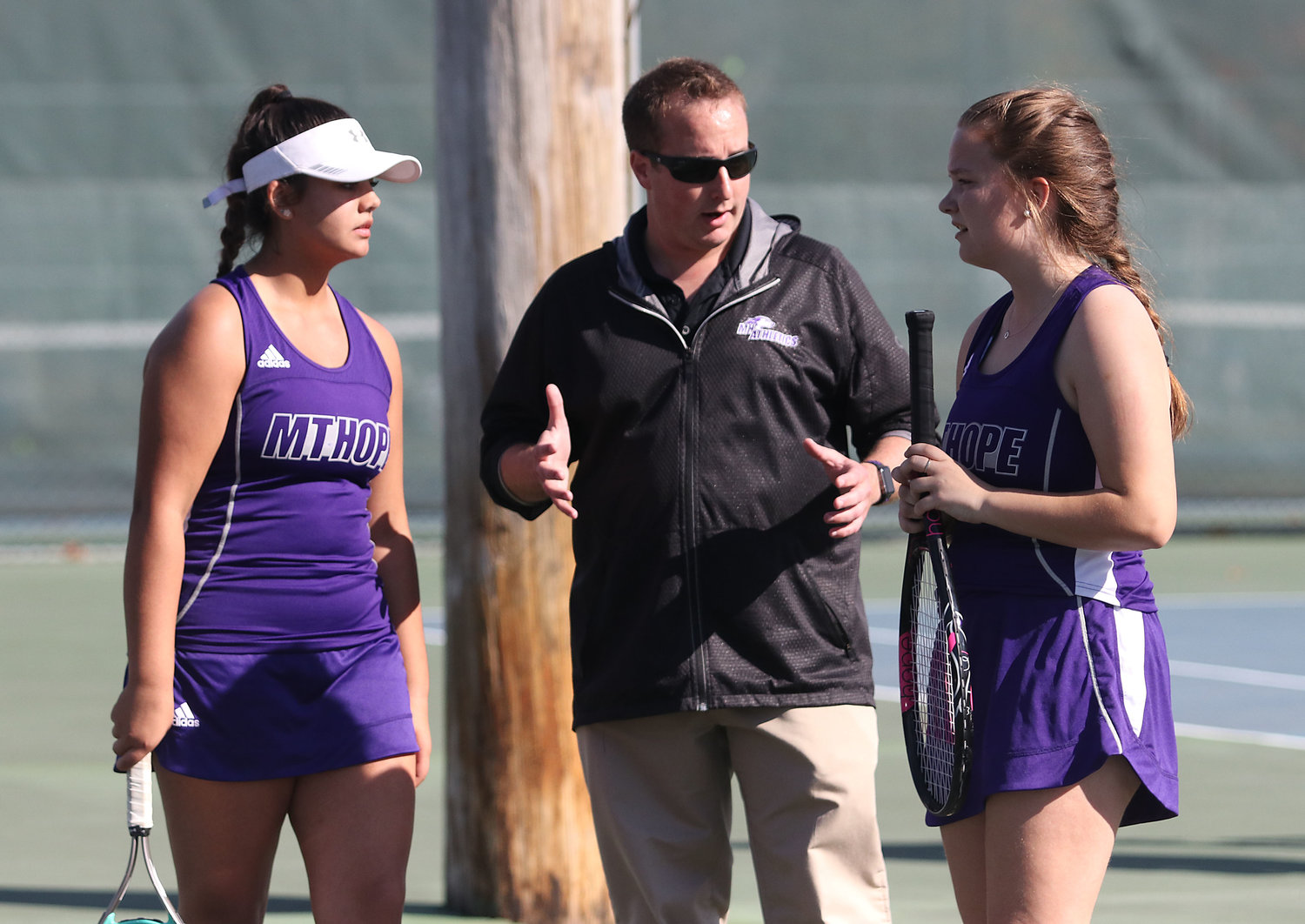 Head coach Geoff Keegan rallies No. 3 doubles team Ally Picard (left) and Olivia Vezina.
