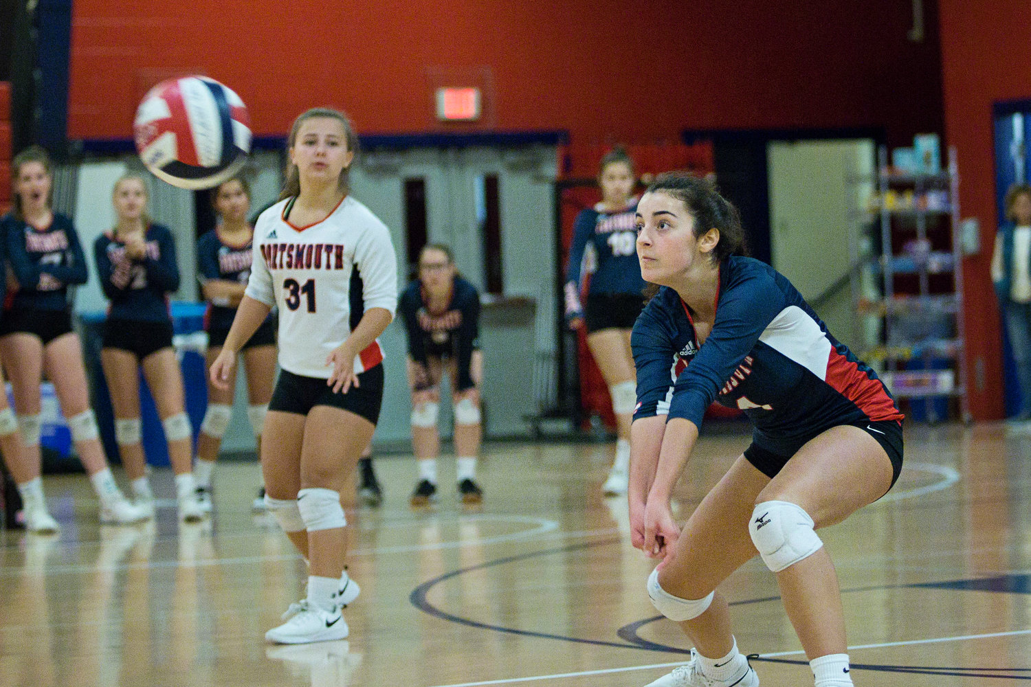 Kylie Donovan (left) looks on as Megan Lehane handles a serve from the Exeter-West Greenwich side.