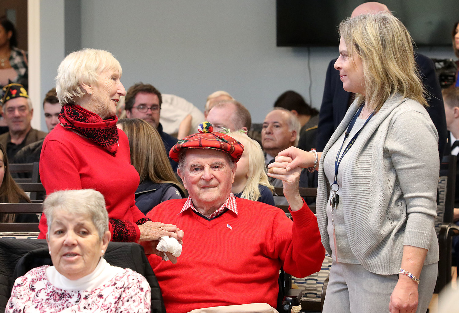Anne Egan (left) holds the hand and dances with husband, Korean War veteran, John Egan along with Rhode Island Veteran's Home employee, Patty Serpa as the Mt. Hope High School band plays the Armed Forces Medley during the Veteran's Day service at the Rhode Island Veteran's Home on Monday afternoon.