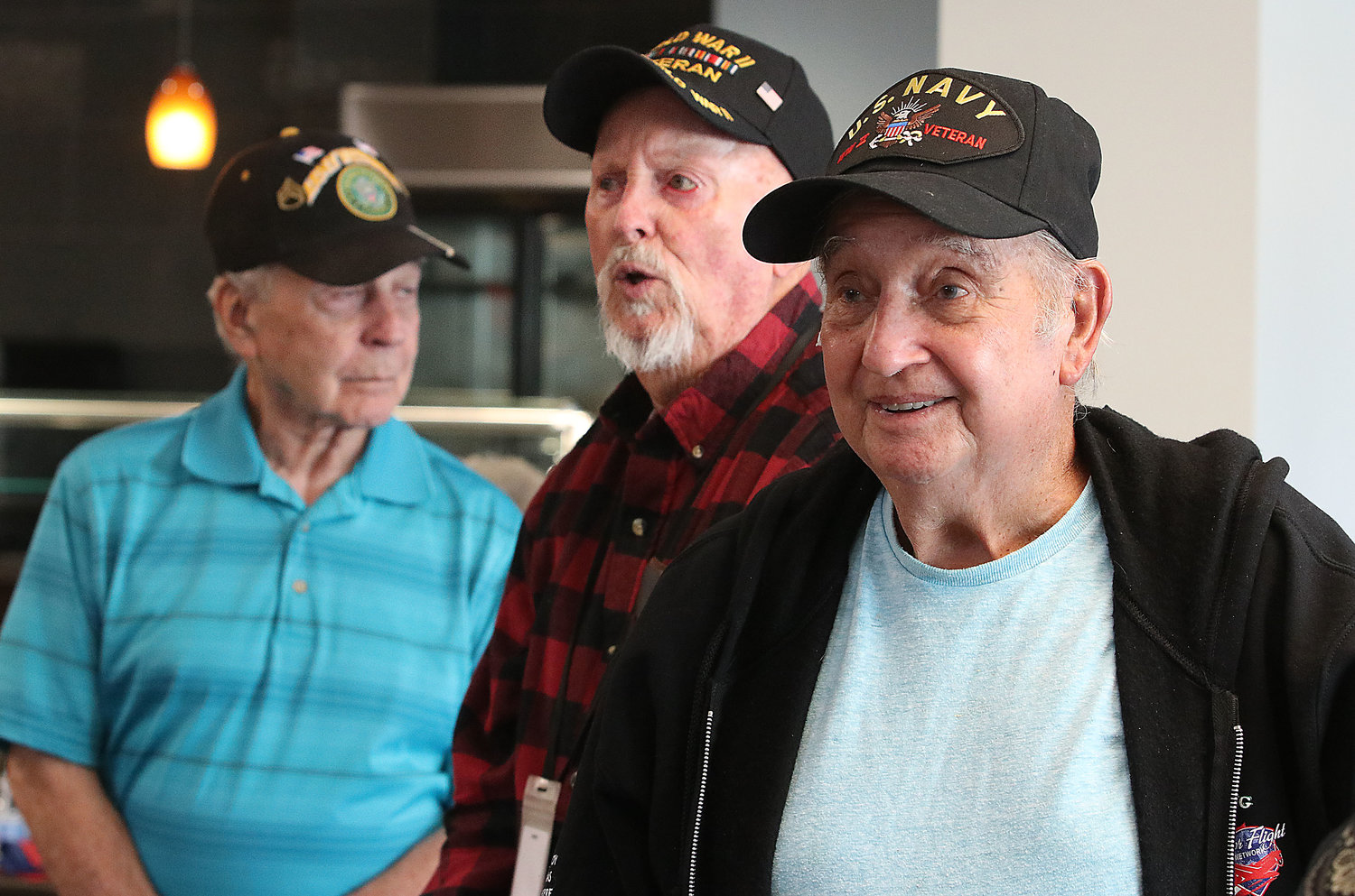 Vietnam veteran Tom Roy (left), WW II veterans Ernie Anderson (middle) and Guy Armillotto stand up during the playing of the Armed Forces Medley.
