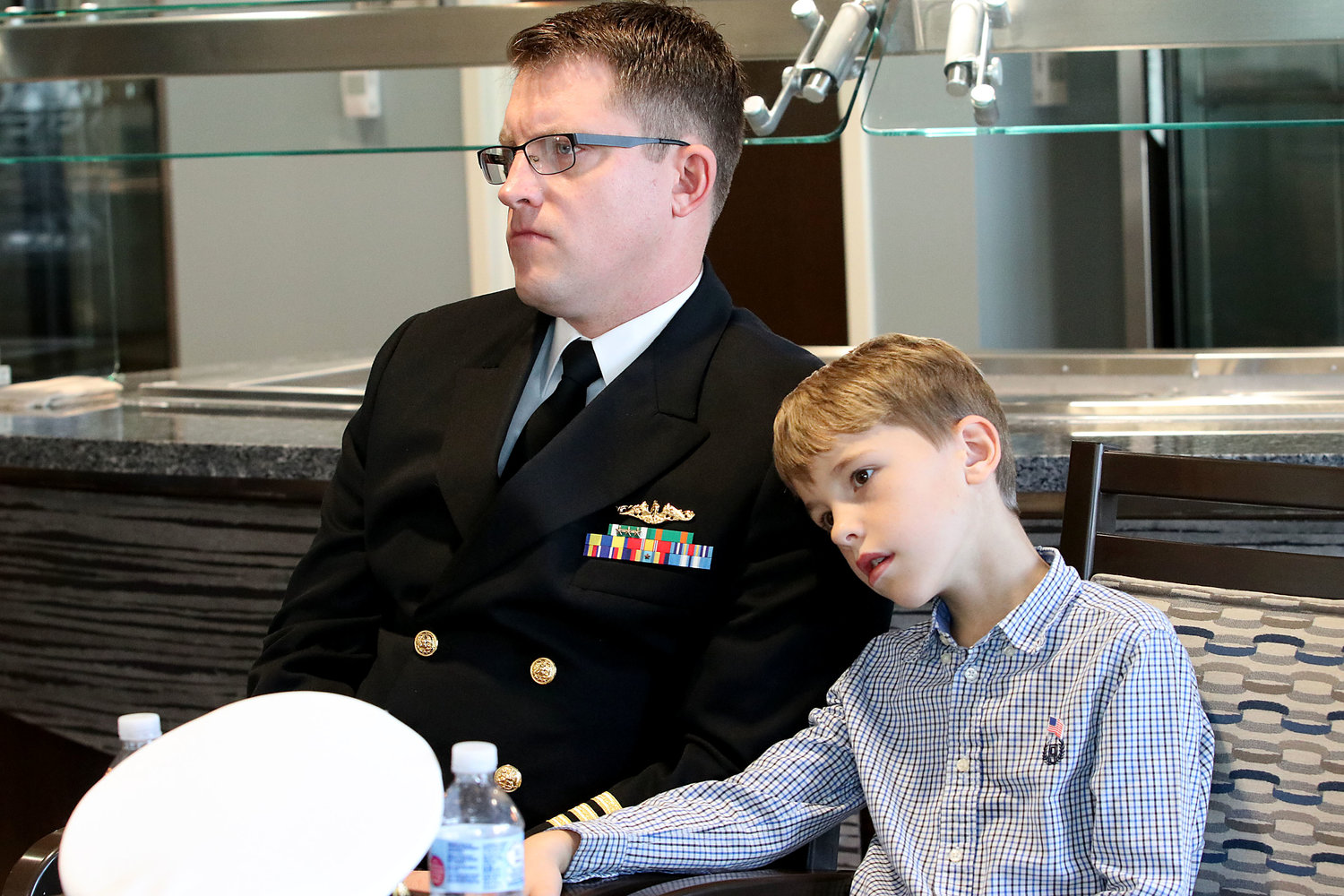 Naval Commander Michael Kendel and son, Thomas, 8, listen on during the ceremony.