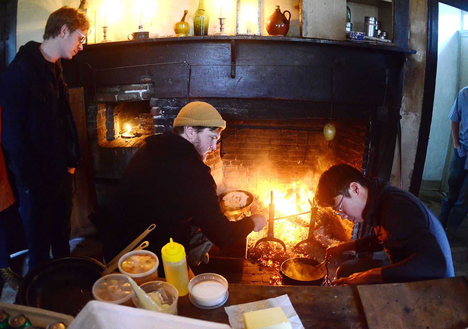 Restaurant owner Ben Sukle (middle) and John Ho (right) cook a meal on an historic open hearth for his Birch and Oberlin employees at Coggeshall Farm on Tuesday.