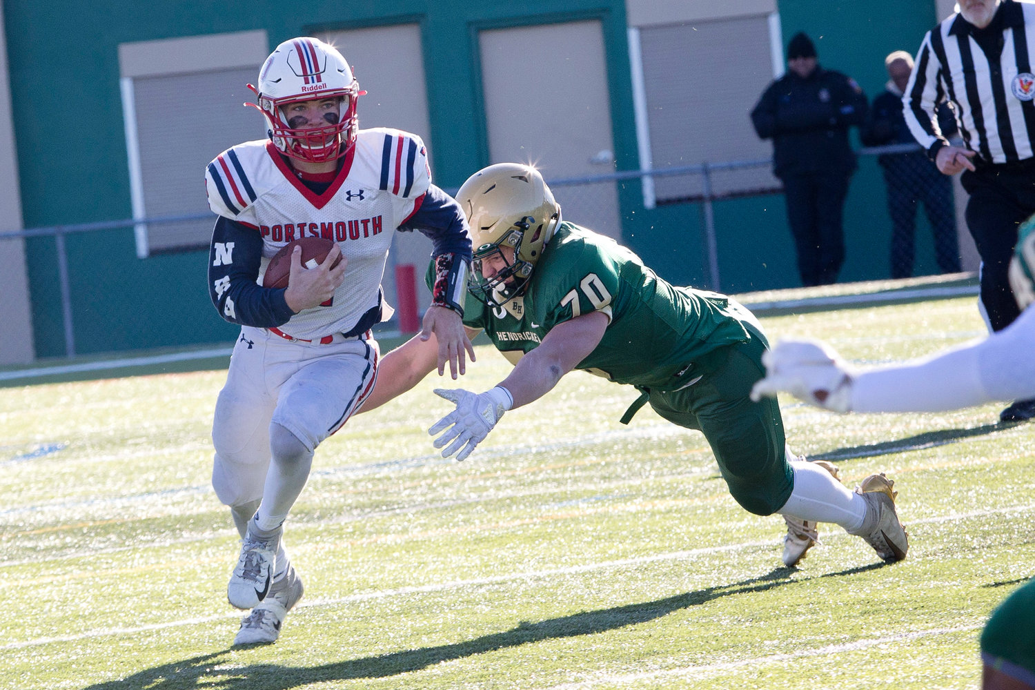 Benny Hurd runs past one Hendricken defender while confronted by another.