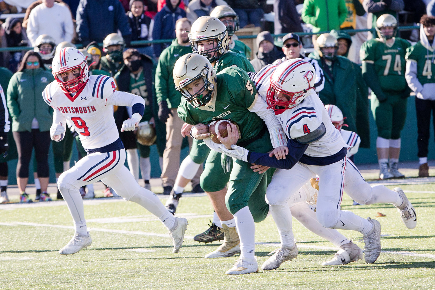 Portsmouth High's Jake Letourneau stops a Hendricken ball-carrier as Christopher Bulk runs around front for support during the Division I Super Bowl game held Saturday in Cranston.