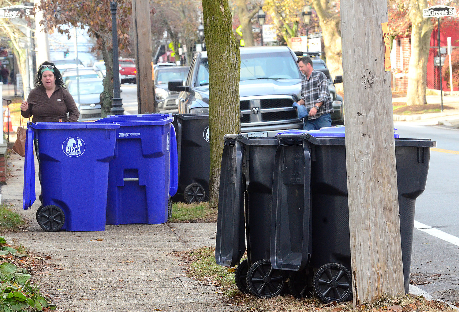 Warrren just launched its new trash and recycling program this week, similar to what Bristol plans for next spring. Pedestrians, bins and cars are shown here on Main Street in downtown Warren. Bristol has decided not to buy these bright blue bins, and it will offer residents smaller version, if they choose.