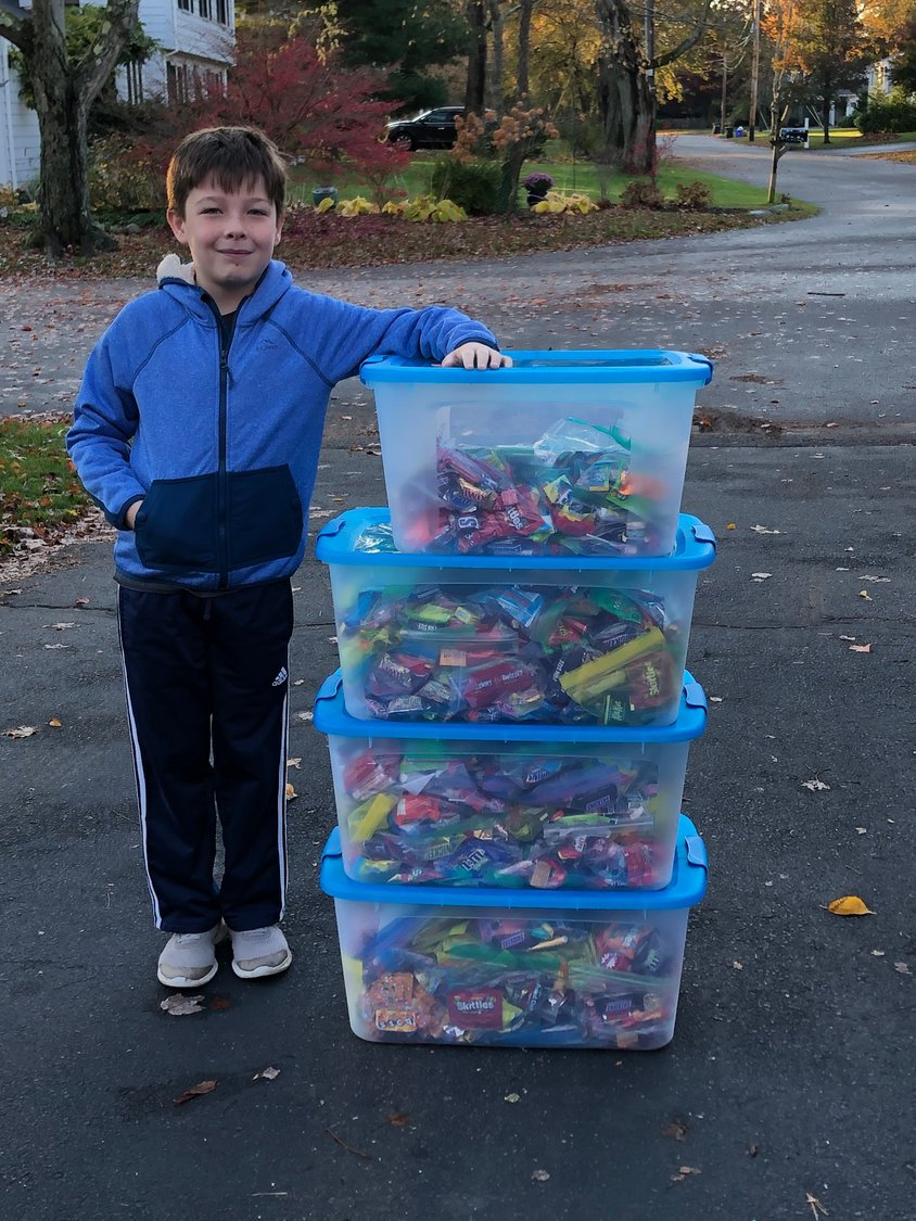 Daniel Shea stands beside bins of the Halloween candy he collected and then later donated to Amos House.
