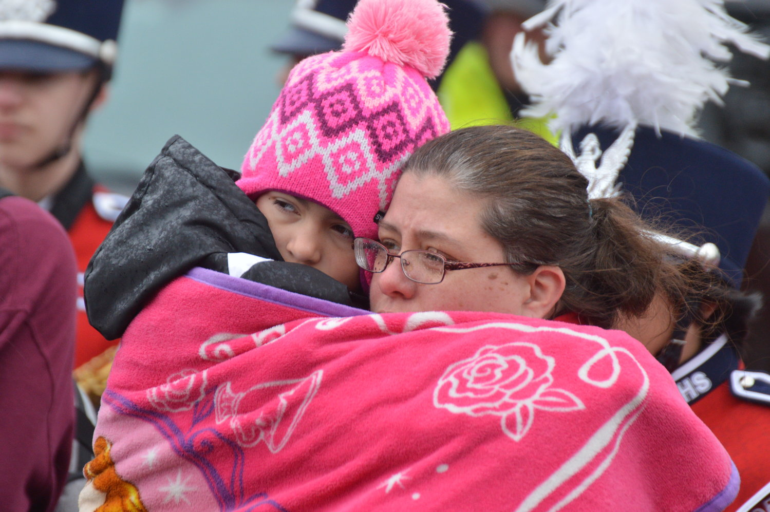 Angelia Williams, 8, snuggles with her mom, Victoria, as they keep warm during the Connor Peckham memorial dedication ceremony.