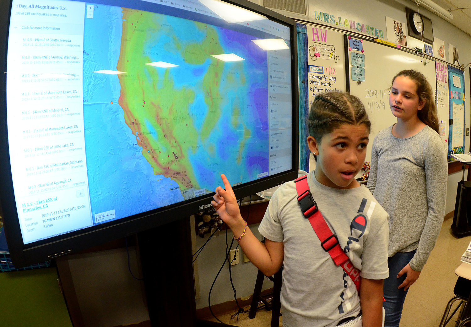 Portsmouth Middle School six-graders Carmine Prestipino (left) and Mia Ruggieri work on a geography lesson using a large smart screen.
