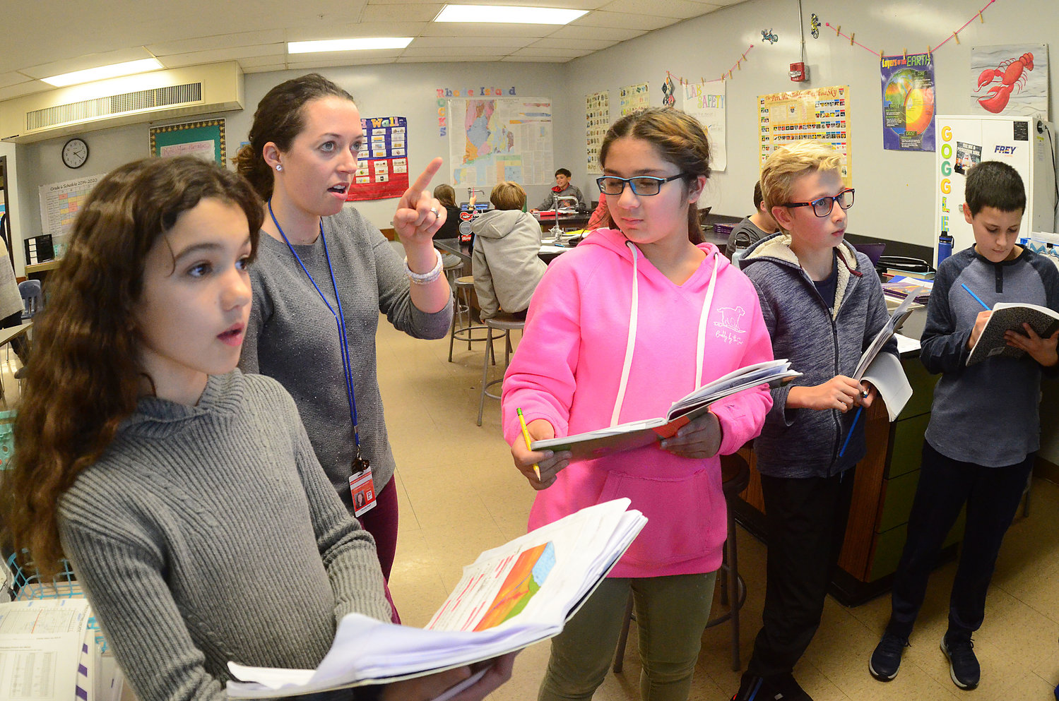 Sixth-graders Lorea Loyola (left), science teacher, Hannah Lancaster, Izzy Chobanian, David Gilmore and Jack Tobin work on a geography problem using a smart screen TV.
