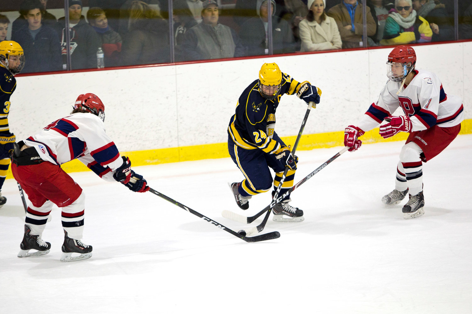 Barrington's Matthew Bates splits a pair of Portsmouth opponents while controlling the puck.