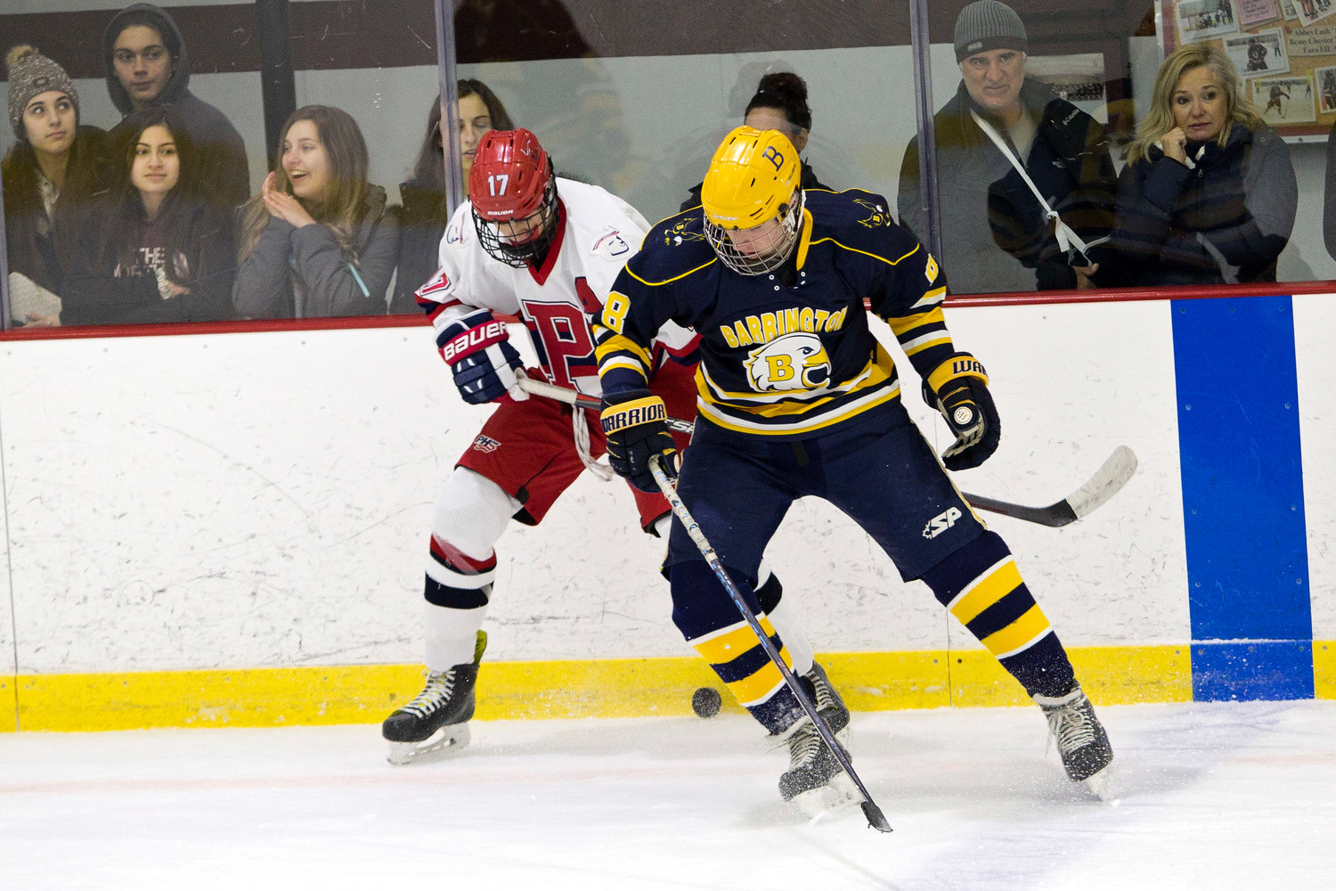 Barrington's Andrew Harris battles a Portsmouth opponent for possession of the puck.