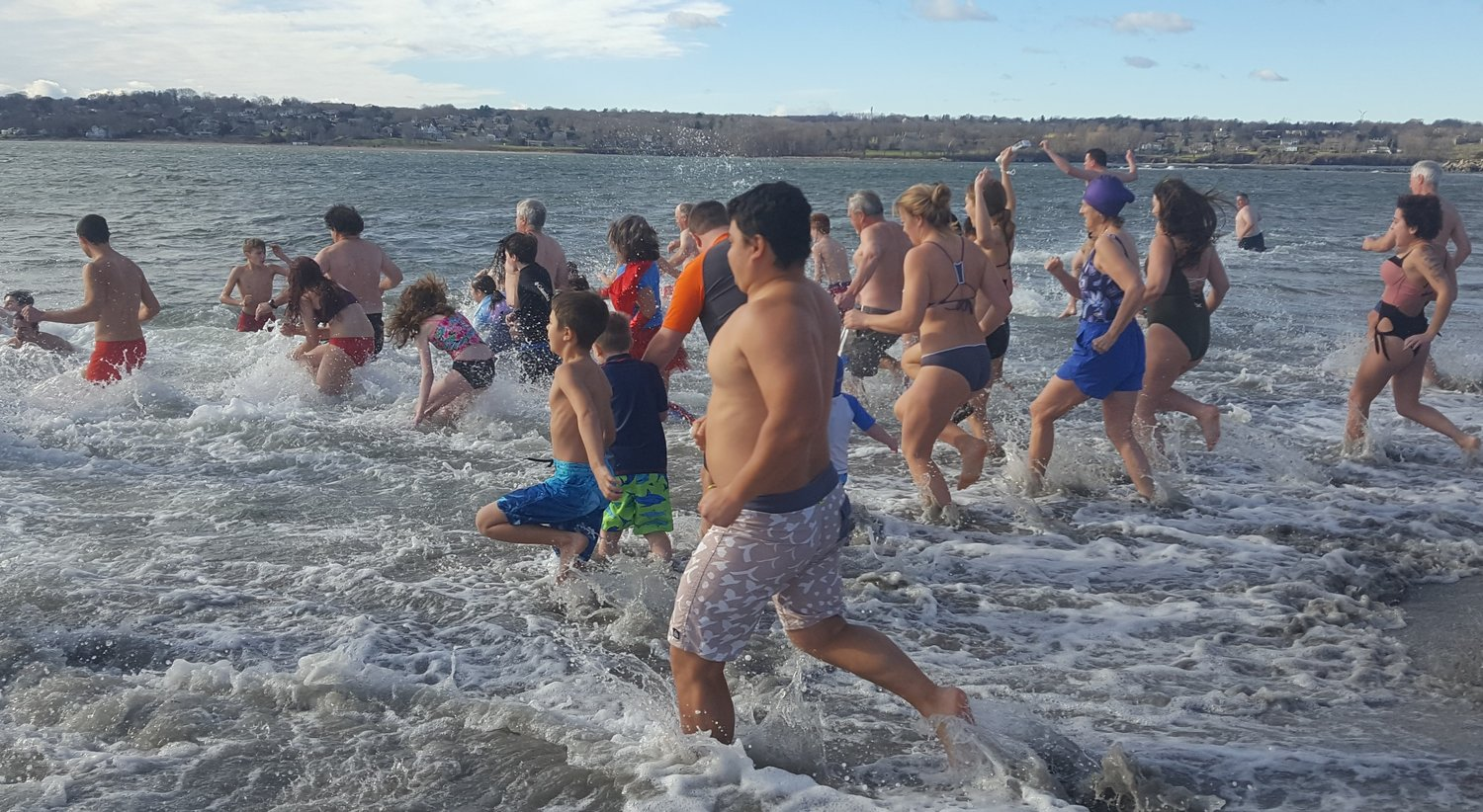 Brave souls dash into the Sakonnet River last New Year's Day at Fogland Beach in Tiverton. This New Year's Day, the event will be back at Grinnell's Beach, its usual home.