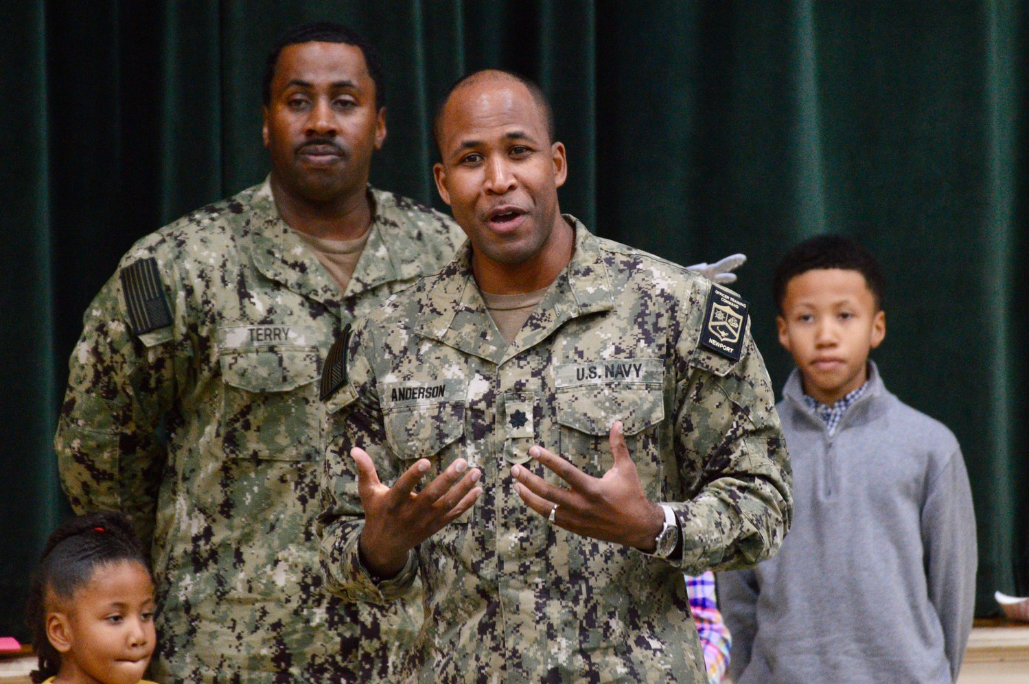 CJ Anderson of Naval Station Newport speaks to Pennfield students while Darrick Terry looks on with this children, Ava and Jadon, both students at the school.