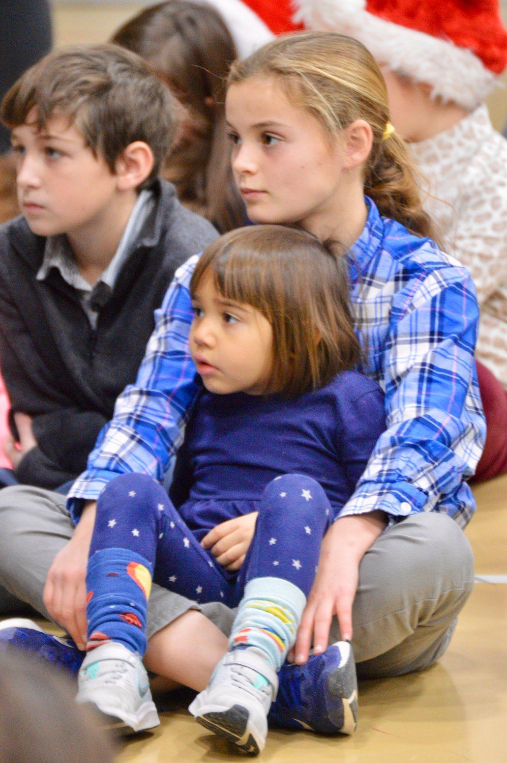 "Charlotte Garcia-Bragiel sits with her ""buddy,"" Maeve Rhatigan, as they listen to a presentation by C.J. Anderson and Darrick Terry of Naval Station Newport, both of whom are also Pennfield parents."