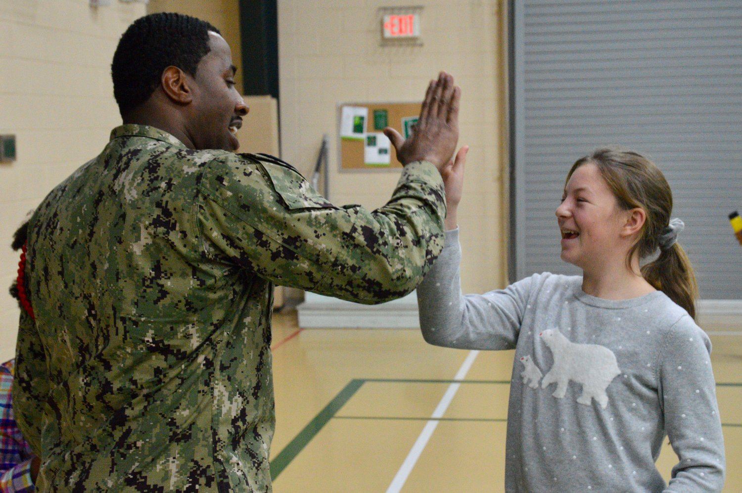 "Darrick Terry of Naval Station Newport gets a ""high five"" from Pennfield School student Summer Magriby before she joined classmates in putting together the ""Panther Packs."""