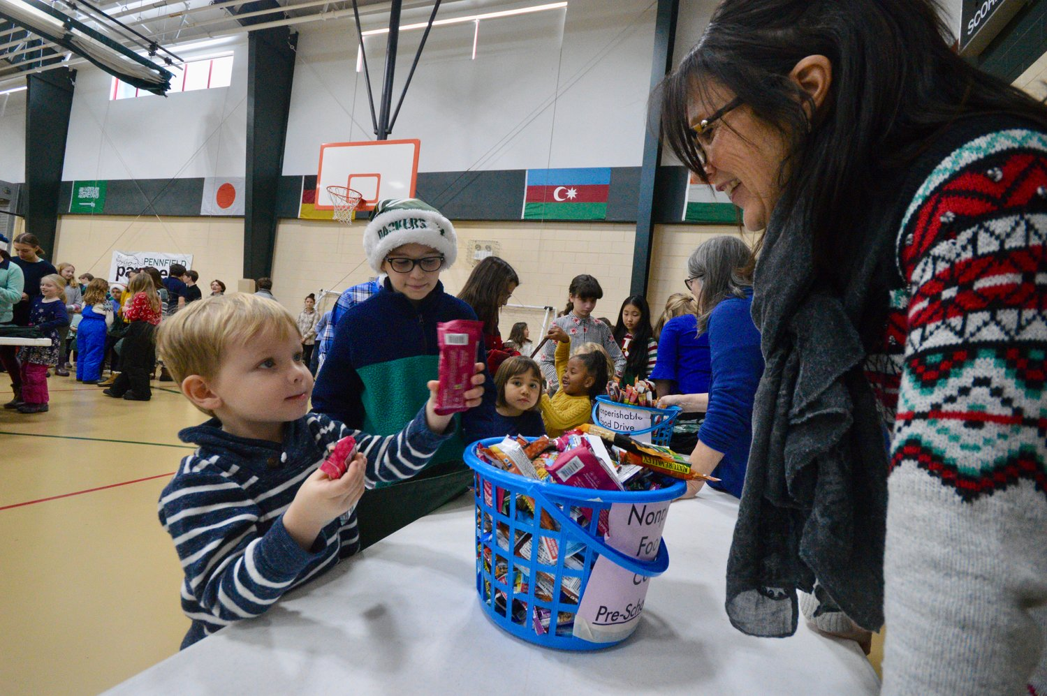 "Pennfield School student Sven Berdahl (left) shows teacher Judy Hall a few items he picked out for a ""Panther Pack,"" as his ""buddy,"" Spencer Mazur, looks on."