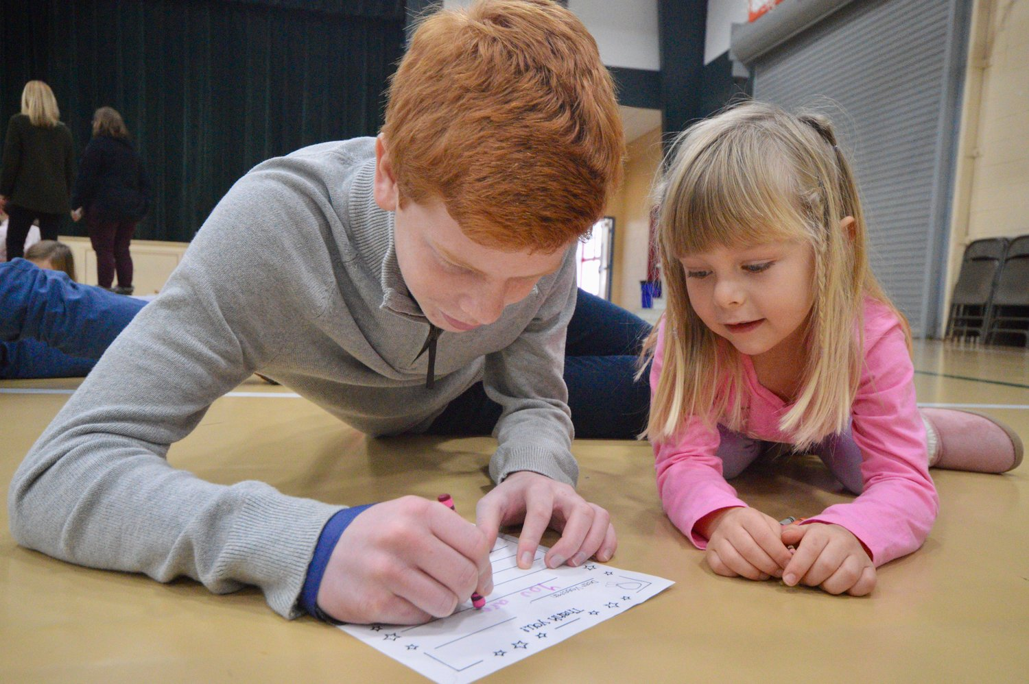 "Audrey Pettit, 5, a student at Pennfield School, gets some help from her ""buddy,"" 13-year-old Wyath Schapiro, as she writes a holiday note to a student at the U.S. Navy's Officer Candidate School in Newport."
