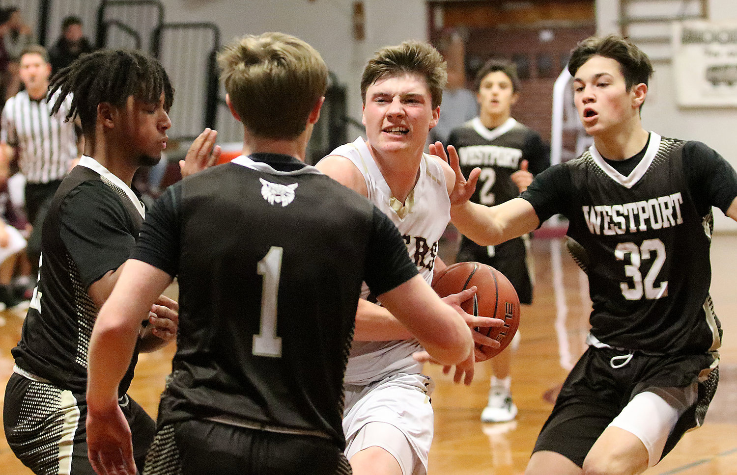 Tigers forward Matt Gacioch readies to drive through a host of Westport players to the basket in the first half.