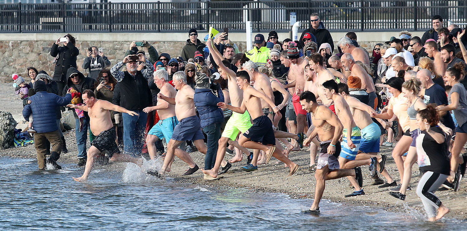 Dozens storm into the wintry waves at Grinnell's Beach Wednesday, January 1.