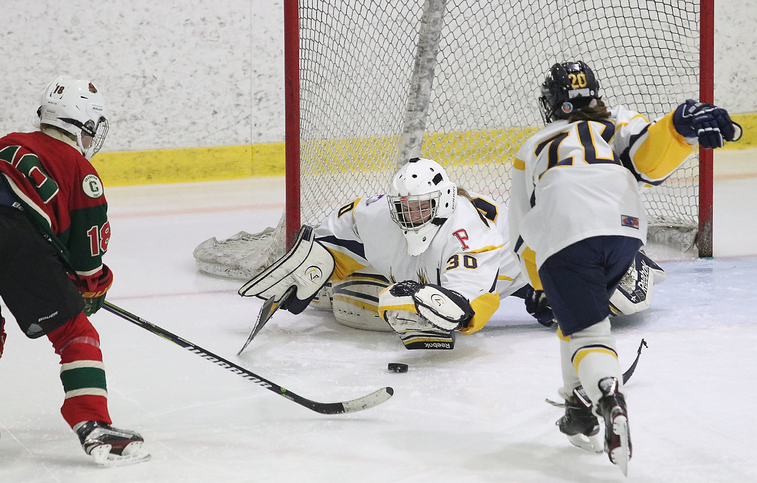 Eagles sophomore goaltender Grace Stephenson jumps on a Cranston shot on goal during their game at Portsmouth Abbey on Thursday night. Mallory Cox skates in to help at right.