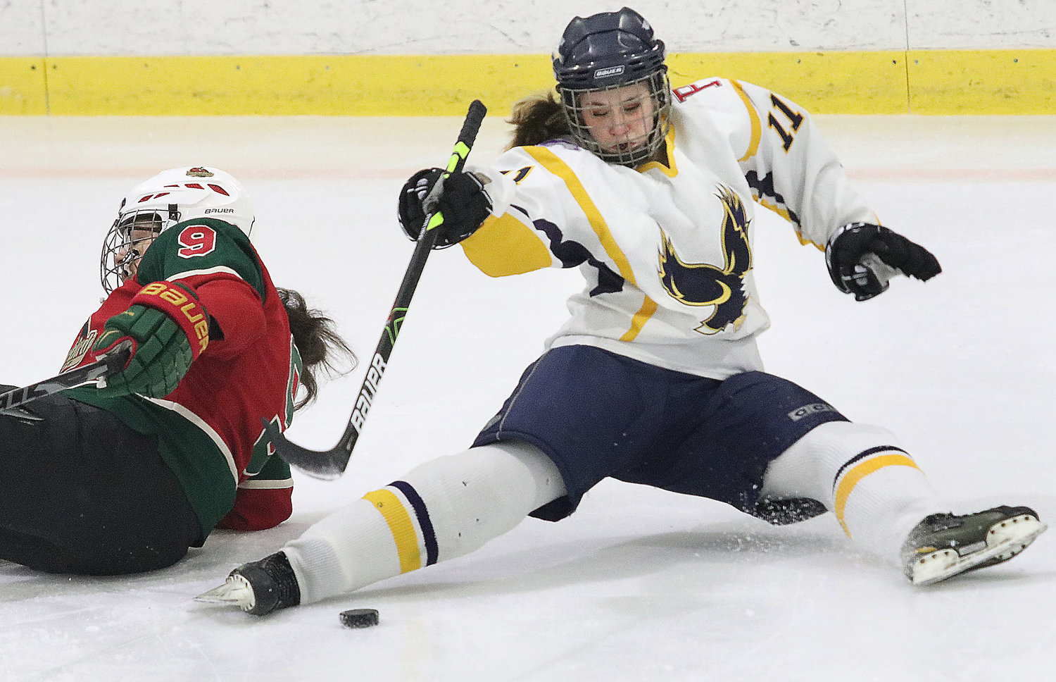 Sophomore Anna Gardiner attempts to play the puck as she falls to the ice after a collision.