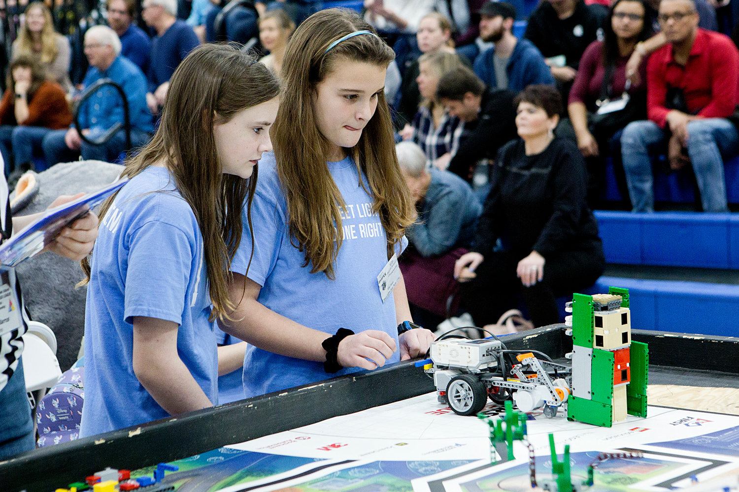 "Marie Claire Walsh (left) and Ellie Jones, of St. Philomena School's ""Street Lights Done Right"" robotics team watch hopefully as their robot navigates the course during round two."