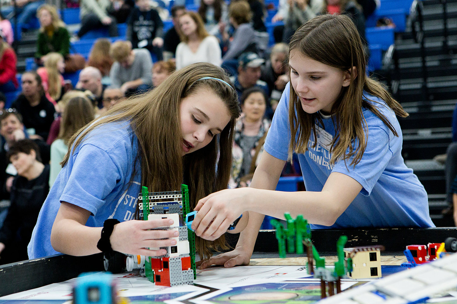 Ellie Jones (left) and Avary Serpa work together to swap attachments on their robot while competing in round two of the First LEGO State Championships.