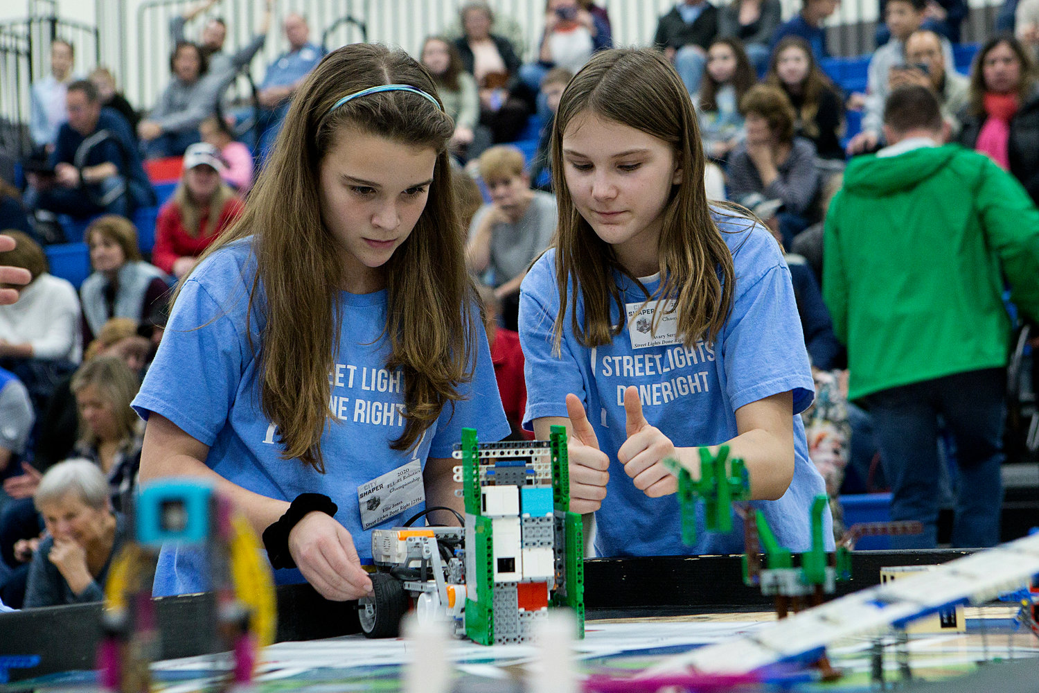 Avary Serpa (right) offers two thumbs up after she and Ellie Jones (left) make adjustments to their robot during round two.