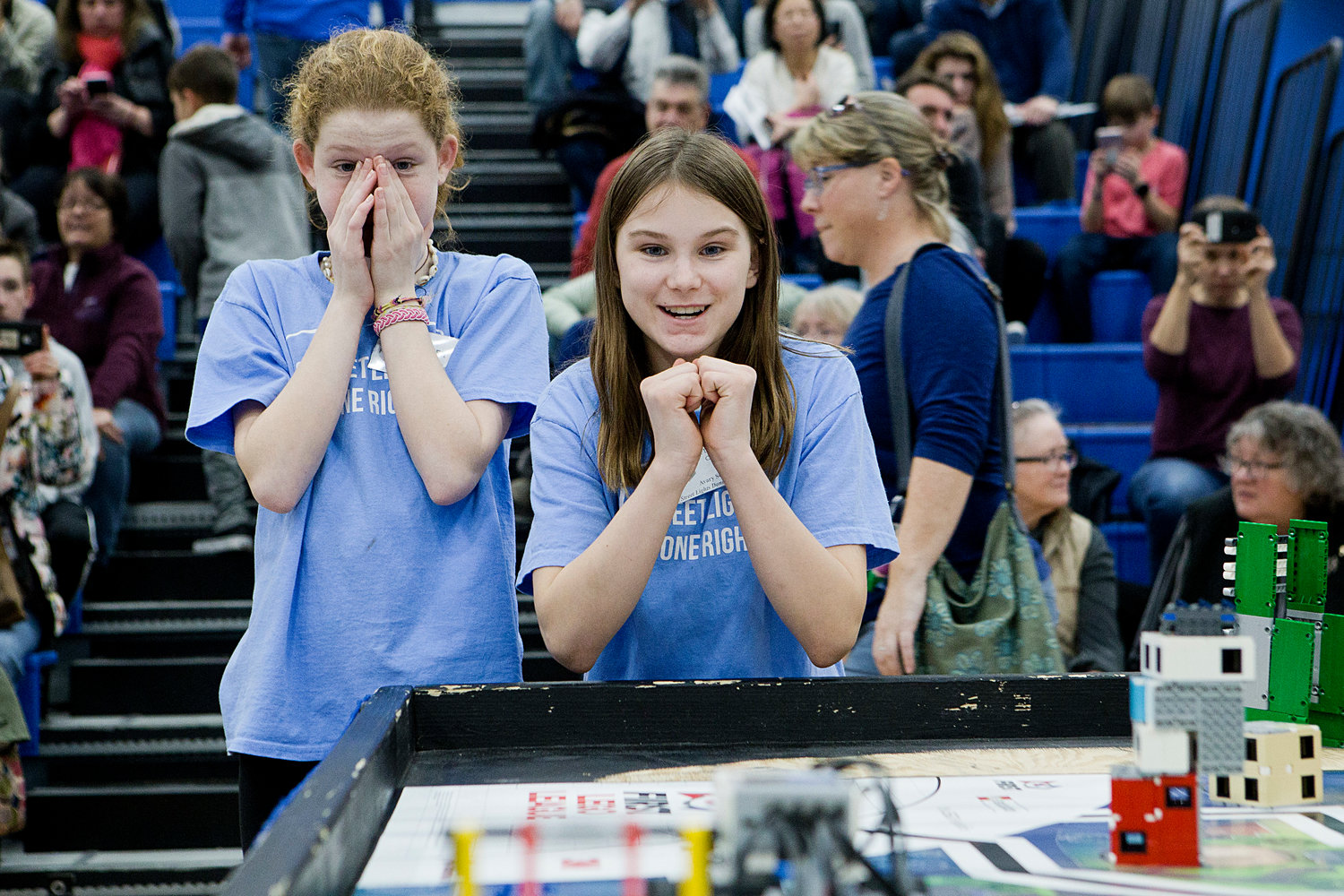 "Caroline Hopkins (left) and Avary Serpa of St. Philomena School's ""Street Lights Done Right"" robotics team make share feelings of nervous excitement as their robot performs during round two of the First LEGO State Championships at Roger Williams University on Saturday."