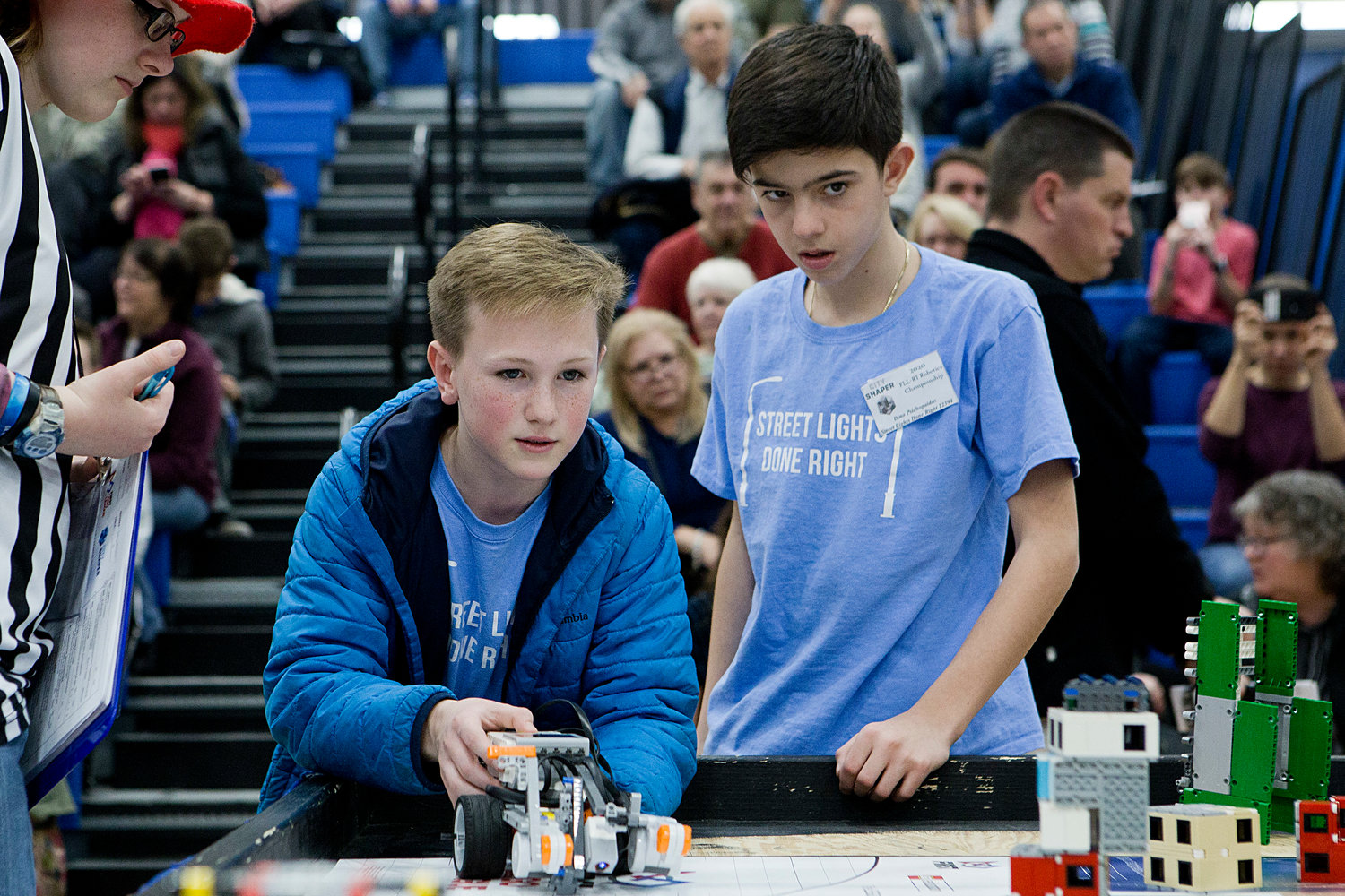 "Mick O'Hara (left) and Dino Psichopaidas of St. Philomena School's ""Street Lights Done Right"" robotics team reset their robot while competing in round two."