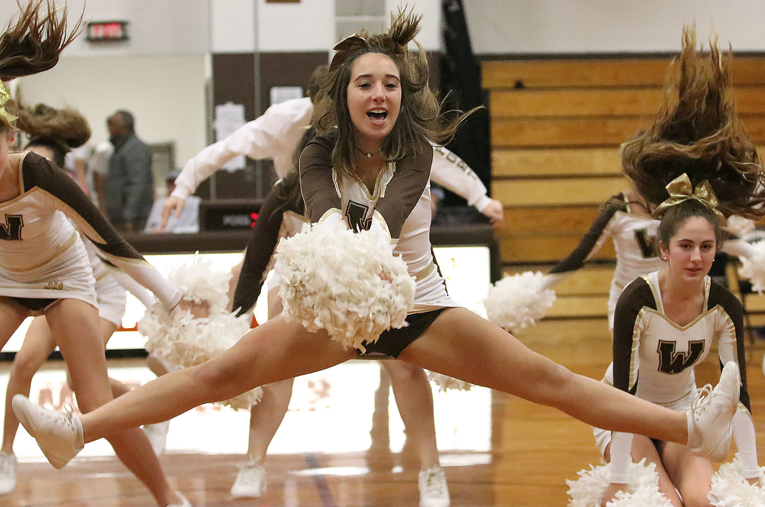 Abby Sousa (middle) and the Westport cheerleaders perform a cheer during halftime.