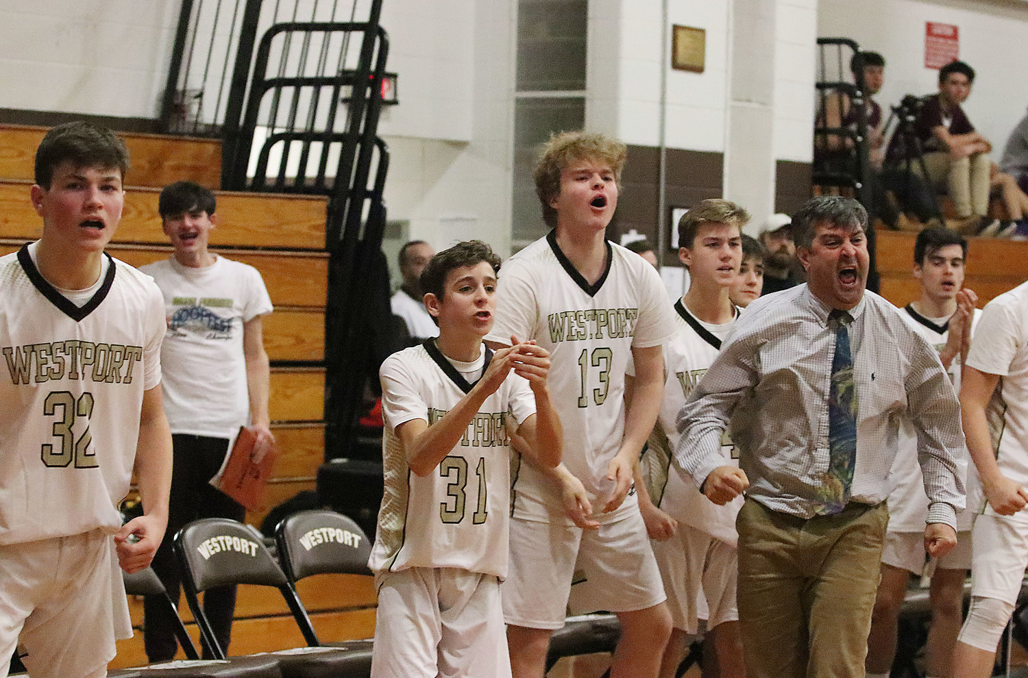The Westport bench and coach Boudria (right) erupt after Aidan Viveiros sinks a three pointer in the second half.