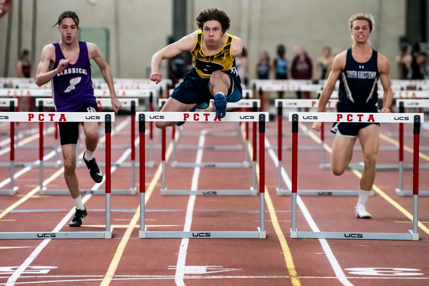 Barrington High School's Walter Joachim-DelPoio (middle) runs to victory in the 55-meter hurdle race.