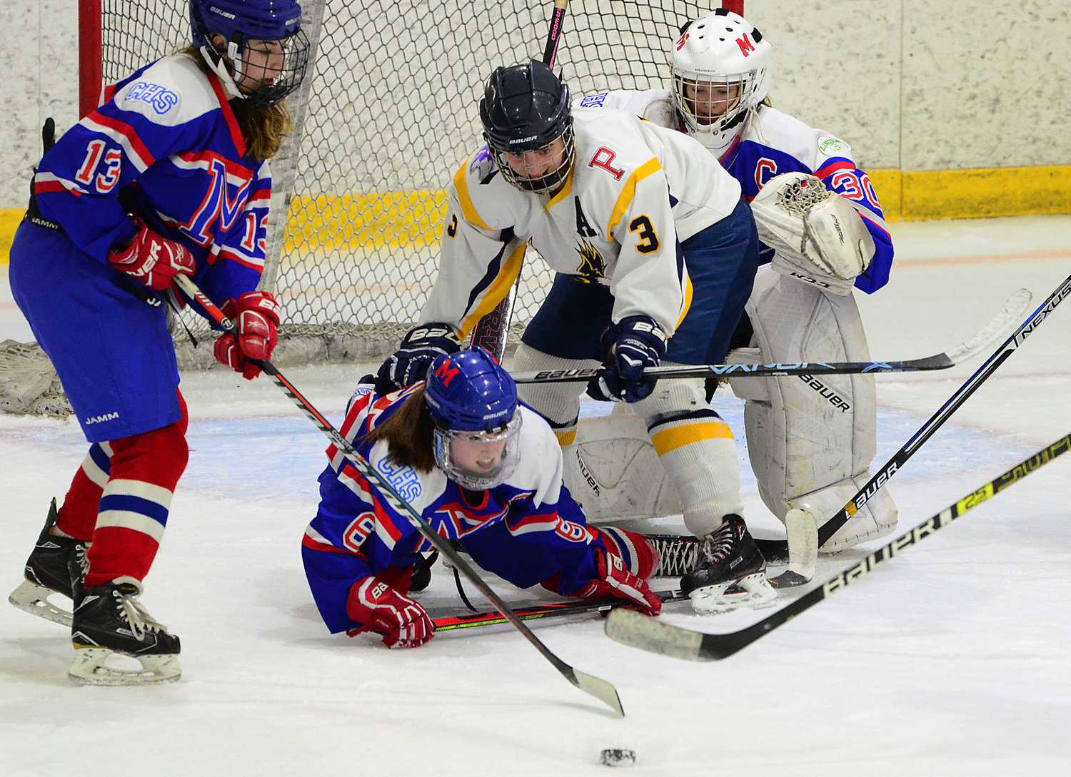 Co-captain and first line winger Maddie Cornell (center) knocks down a Mount defender while chasing a rebound.