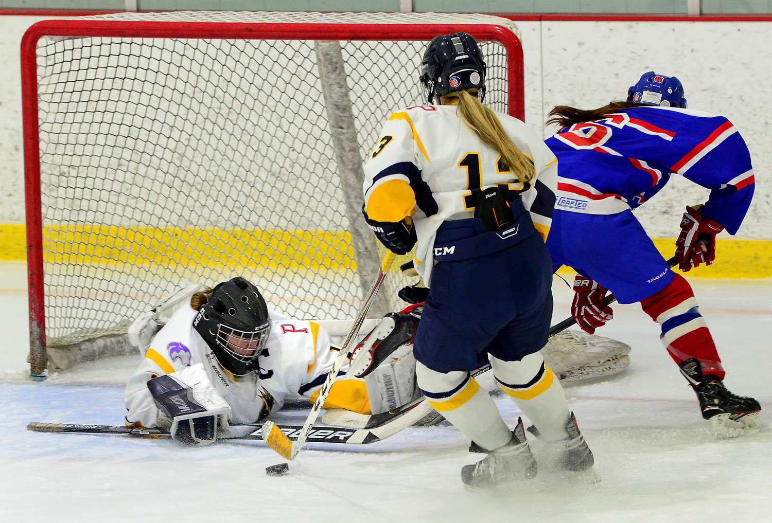 Eagles co-captain and senior goaltender Ellee Kopecky makes a save as teammate Alexandra Phelps collects the puck.